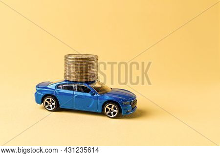 Blue Toy Car Is Carrying A Stack Of Coin Against Yellow Background. Saving Money For A Car. Car Inve