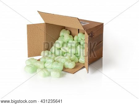 Shipping Peanuts Spilling Out Of The Parcel Box Laying On Its Side, Isolated On A White. Brown Cardb