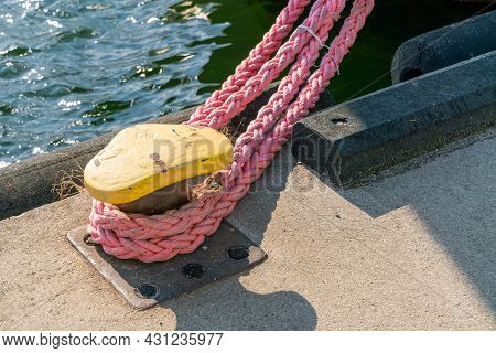 Detail Closeup Shot Of Yellow Steel Harbour Knob With A Strong Pink Rope Attached To It, Securing A