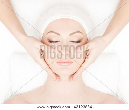 Portrait of young and beautiful woman getting spa treatment isolated on white