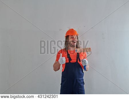 An Employee With Long Hair In Overalls Stands In An Apartment