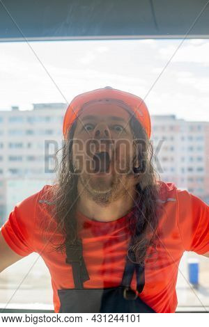 Funny Engineer In A Helmet Makes A Face Behind The Glass