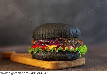 Fresh Tasty Black Burger On A Black Background. Close-up. Copy Space