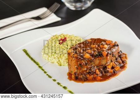 Beef Tenderloin And Basil Risotto On A Porcelain Plate