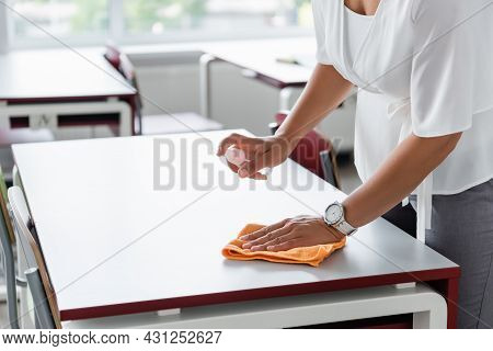 Partial View Of African American Teacher Disinfecting Desk With Antiseptic