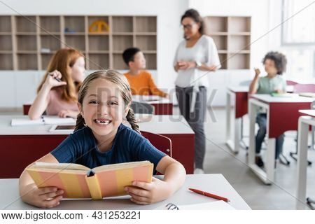 Overjoyed Girl Holding Book Near Blurred Classmates And African American Teacher