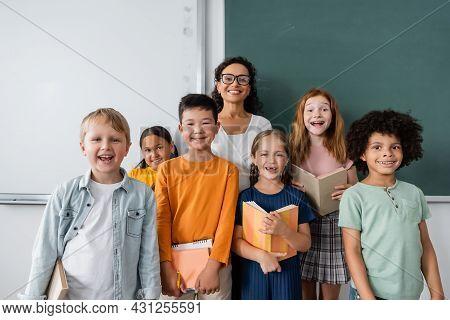 African American Teacher And Joyful Multiethnic Schoolchildren Smiling At Camera In Classroom