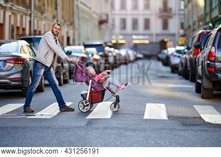 Girl 3 Years Old In Baby Carriage And Father On Crosswalk Near Traffic.