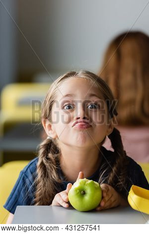 Playful Girl Sticking Out Tongue While Grimacing Near Apple In School Canteen