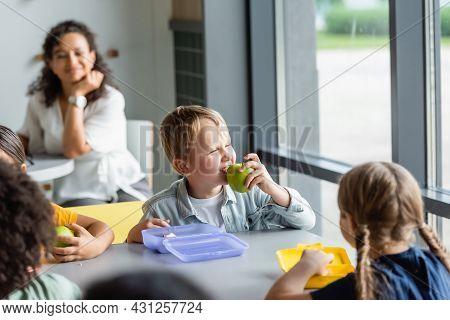 Boy Eating Apple Near Classmates And Blurred African American Teacher