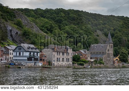 Dinant, Wallonia, Belgium - August 8, 2021: Houses And Church Of Saint Paul Des Rivages Along Meuse