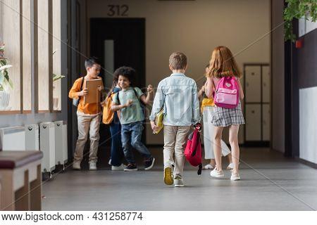 Multiethnic Schoolkids With Backpacks And Notebooks In School Corridor