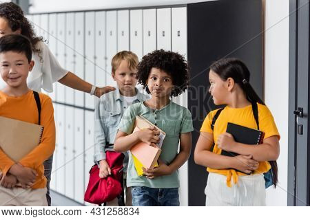 Thoughtful African American Boy Puffing Out Cheeks Near Multiethnic Classmates And Teacher In School
