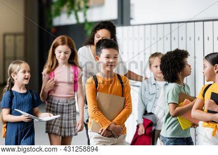 Multiethnic Schoolkids Walking Along School Corridor Near Blurred African American Teacher