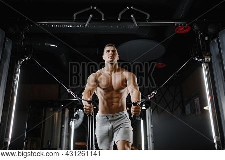 Brutal Guy Bodybuilder Model With A Naked Torso, Trains In The Gym. Heavy Workout, Fitness And Bodyb