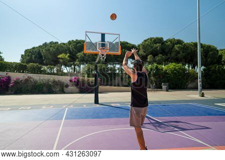 Rear View Of Male Sportsman Playing Basketball Throwing The Ball At Playground, View From Behind. Pr