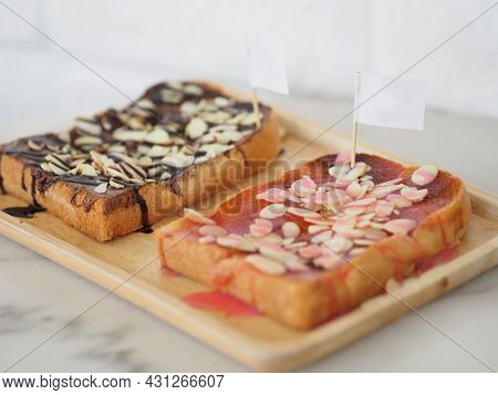 Bread Topped With Milk Strawberries Topped With Almonds Placed In A Wooden Plate Stick White Paper F