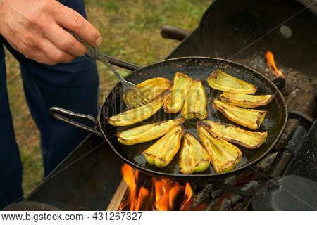 Slices Of Green Pepper Is Frying On Frying Pan With Oil In Chargrill, Closeup View. Man Is Flipping