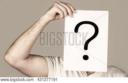 Portrait Of Man, Peeking Behind Of Interrogation Symbol. Male Isolated. Man A Question. Doubtful Man