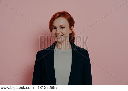 Successful Pretty Red-haired Woman Looking At Camera With Confidence And Pleasant Smile, Standing Is