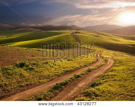 a long and winding rural path crosses the hills at the sunset