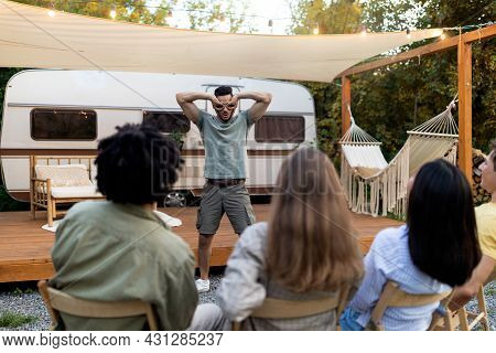 Group Of Diverse Millennial Friends Playing Charades Near Trailer, Trying To Guess Word On Autumn Ca