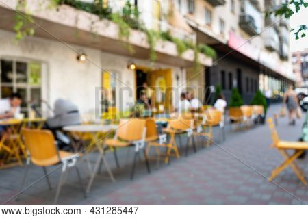 Blurred Abstract Background Of Outdoor Cafe Or Restaurant. Outdoor Cafe With Tables And Chairs. Stre