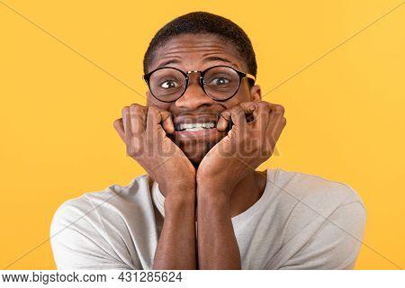 African American Man Biting Nails In Panic On Yellow Studio Background. Horrified Black Guy Feeling
