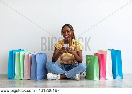 Millennial Black Woman Shopaholic Purchasing Online, Using Smartphone