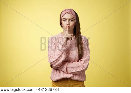 Keep Mouth Shut. Serious-looking Bossy Attractive Young 20s Woman In Sweater, Headband Shushing Maki