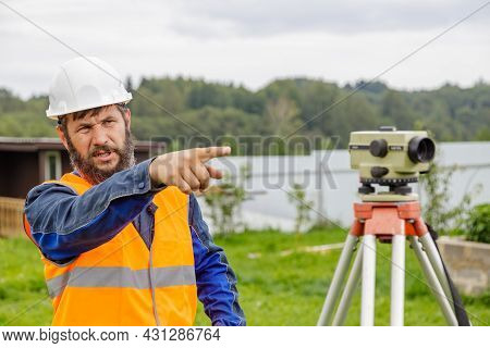 A Civil Engineer With An Optical Level Waves His Hand To Control Colleagues From A Distance. A Beard