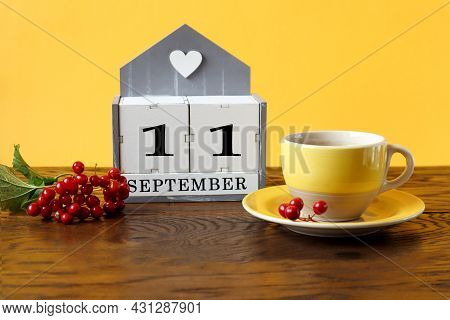 Calendar For September 11 : The Name Of The Month In English, Cubes With The Number 11, A Yellow Cup