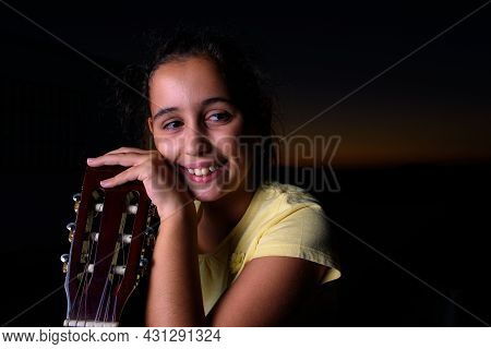 A Brunette Girl, During Sunset, Looks Fondly At Her Guitar, After Having Been Playing Outdoors.
