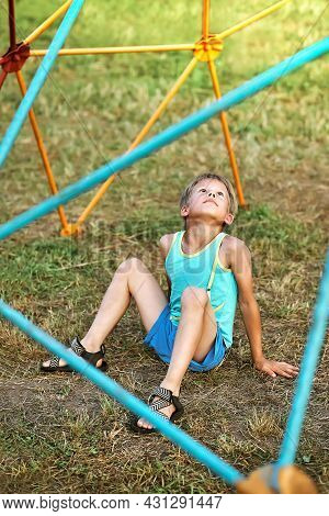 Adorable Little Boy In Blue Clothes Sits On Green Grass Under Colorful Climbing Play Set Looking Upw