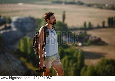 Guy Looking At Binoculars In Hill. Man In T-shirt With Backpack. Young Caucasian Man During Hike In