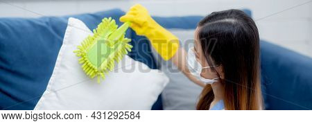 Young Asian Woman In Face Mask And Gloves Cleaning Dust With Duster On Sofa And Cushions At Home, Gi