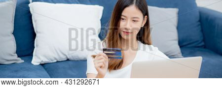 Young Asian Woman Sit On Sofa Using Laptop Computer Shopping Online With Credit Card Buying To Inter