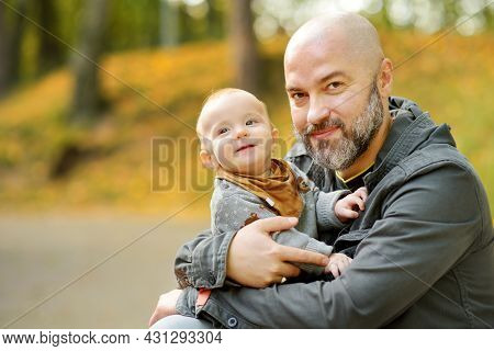 Cute Little Baby Boy In His Fathers Arms. Dad And Son Having Fun On Sunny Autumn Day In City Park. S