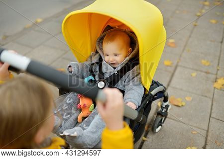 Sweet Baby Boy Wearing Warm Clothes Sitting In A Stroller Outdoors. Little Child In Pram. Infant Kid