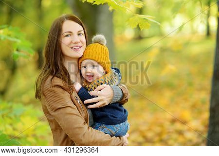 Cute Little Baby Boy In His Mothers Arms. Mom And Son Having Fun On Sunny Autumn Day In City Park. A