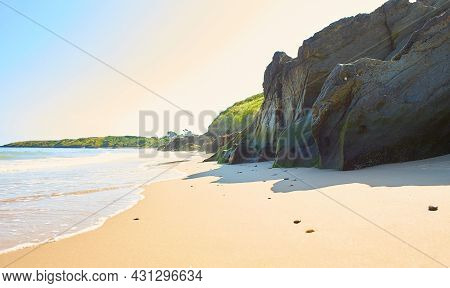 Rocky Beach With Green Moss On The Daytime With The Sea Background.