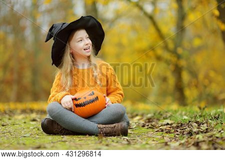 Cute Young Girl Wearing Black Witch Hat Holding A Small Pumpkin. Kid Trick Or Treating On Halloween.