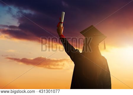 A Pretty Female Student, Celebrating Her Graduation And Stand Against The Idyllic Sunset View With H