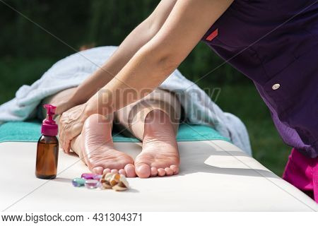 Massage Of Legs, Female Feet With Oil, Stones Outdoors. Close Up Photo Of Woman Foot And Therapists