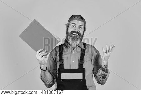 Bearded Storekeeper. Supplier Of Goods. Delivery Man In Cap Holding Clipboard Looking Information. C