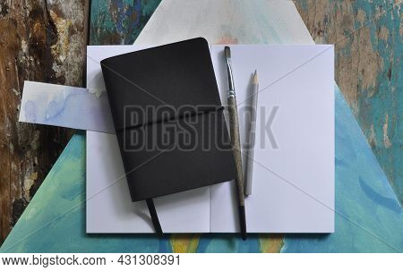 Black Blank Notebook Or Book Cover On Rustic Painted Wooden Background. Lettering Or Art Flat Lay Mo