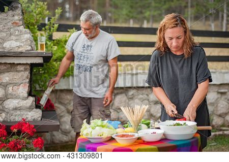 Bbq Grilling Party. Couple In Garden Making Barbecue Outdoors. Food, People And Family Time Concept