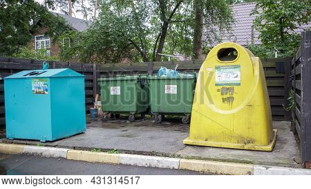 Four Plastic And Metal Garbage Bins For Sorting Waste In The Courtyard Of A Residential Street. Garb