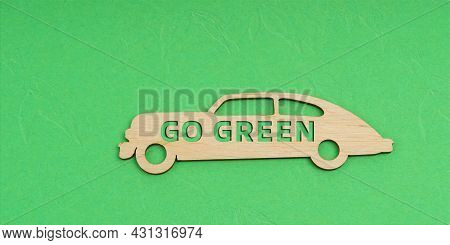 Ecology And Transportation Concept. On A Green Background, A Wooden Car With The Inscription - Go Gr