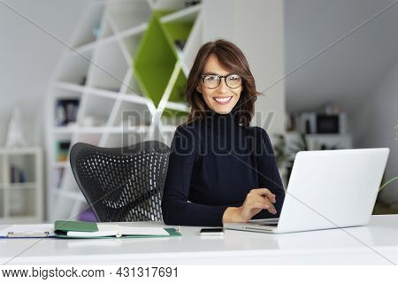 Attractive Businesswoman Wearing Eyewear And Turtleneck Sweater While Working On Her Laptop